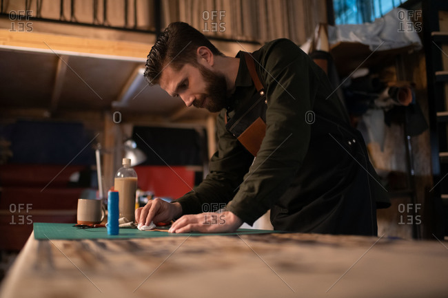 Bearded craftsman wetting leather on workbench