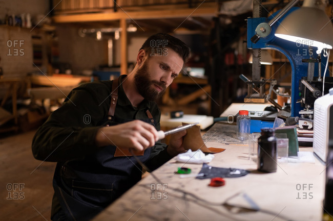 Focused craftsman using pyrography machine on leather