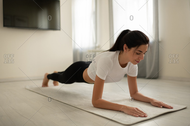 Young female planking on mat at home