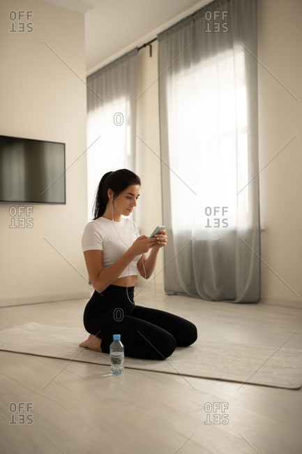 Female sitting on mat and browsing smartphone