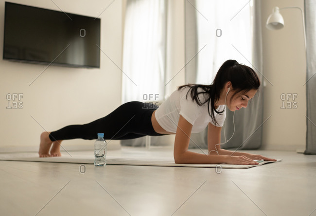 Young female planking with earphones and smartphone