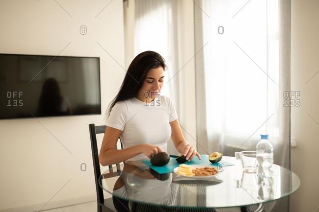 Content female preparing healthy food in apartment