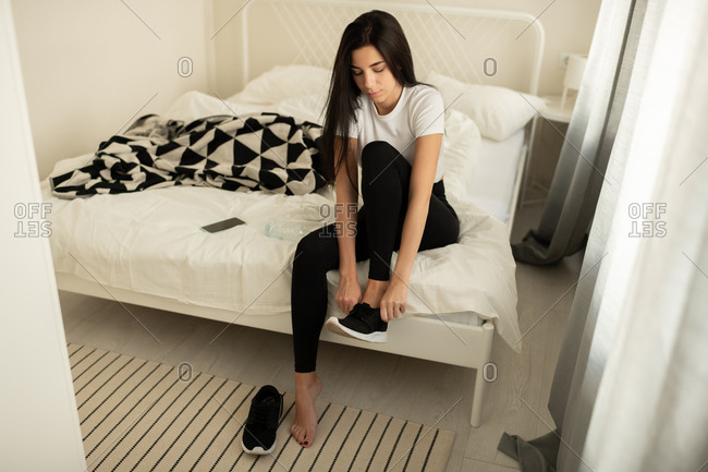 Athletic female preparing for workout in modern bedroom