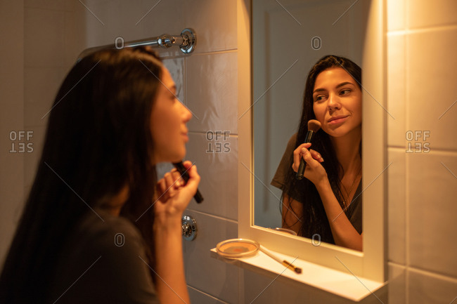 Positive young female doing makeup before mirror