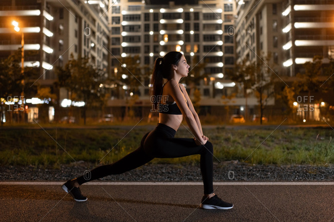 Fit sportswoman stretching legs during night workout