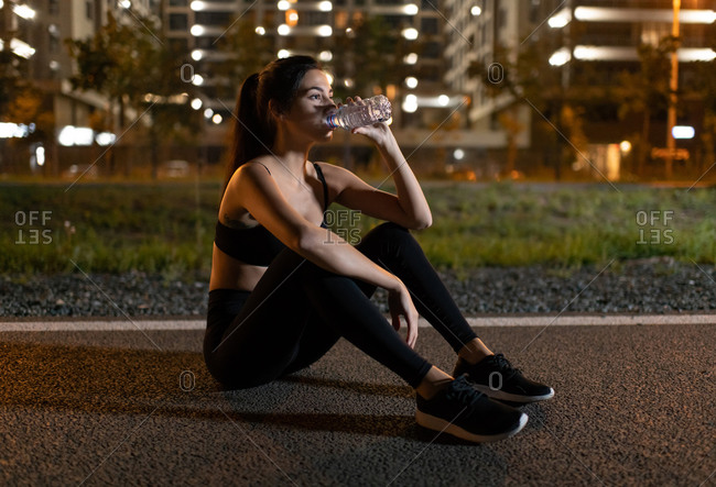 Sportswoman drinking water on track at night