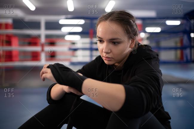 Female boxer wrapping bandage around hand