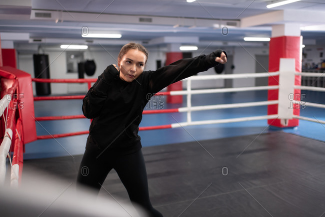 Energetic sportswoman practicing boxing movements on ring