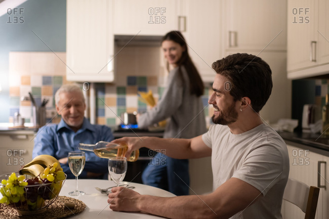 Cheerful man pouring wine for father