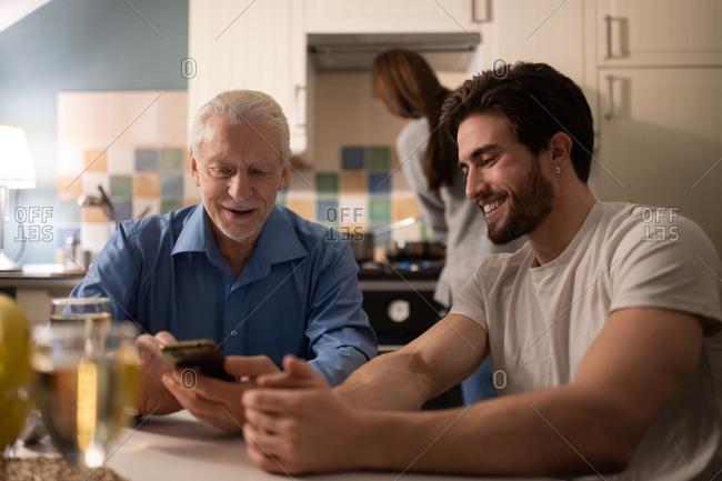 Mature man browsing smartphone near son