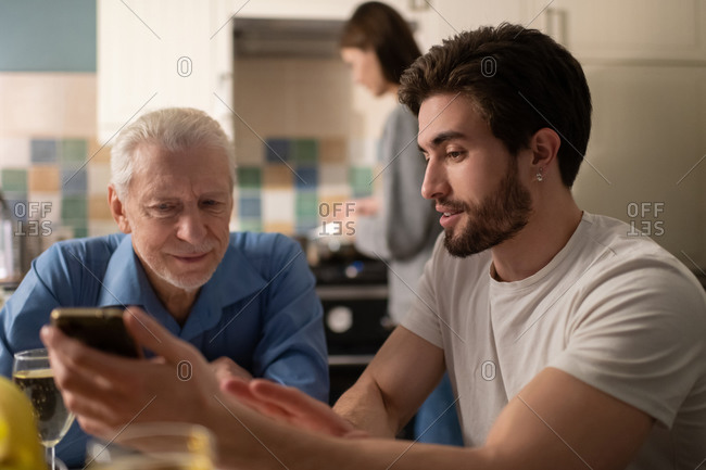 Bearded man sharing photos with father