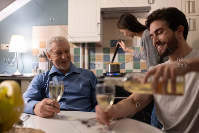 Happy senior father watching son pouring wine
