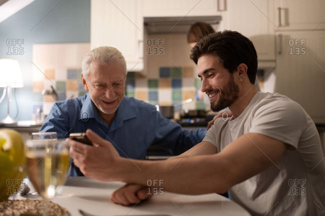 Senior father supporting son while watching photos together