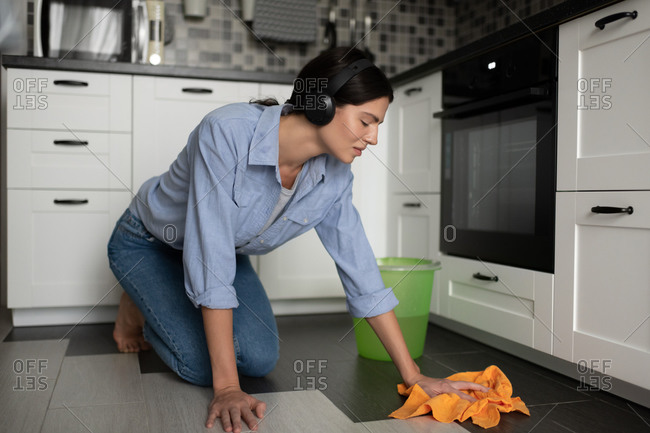 Woman cleaning home and listening to music with headphones