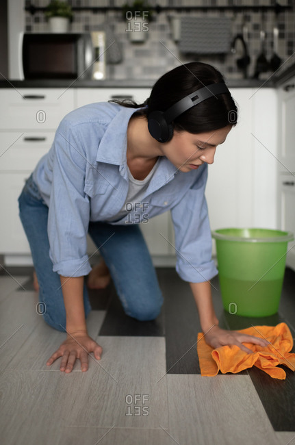 Young woman with headphones washing floor in kitchen