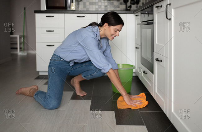 Cheerful woman washing floor in kitchen
