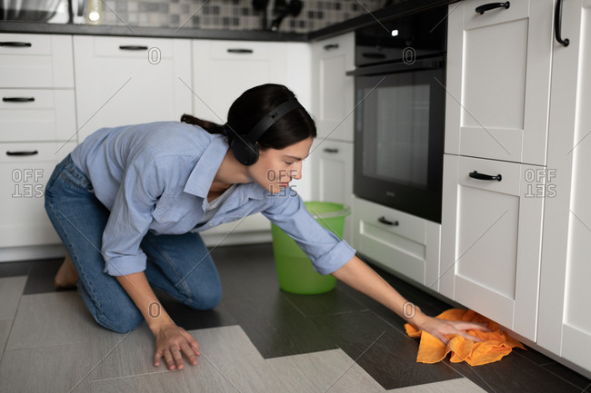 Casual woman listening to music and washing floor in kitchen