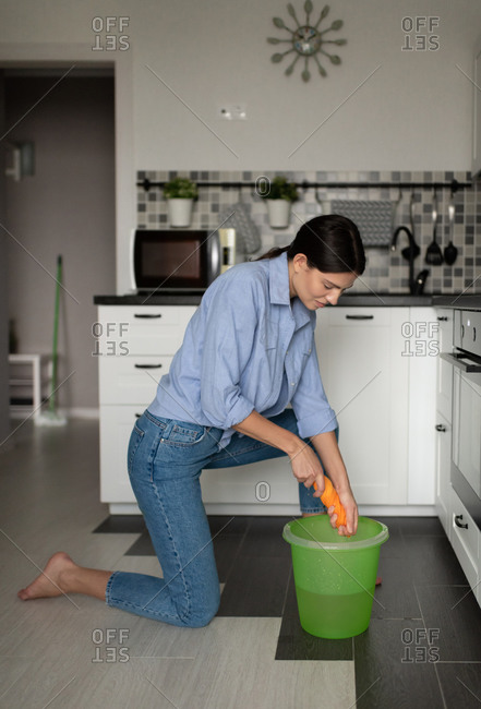 Woman cleaning home and squeezing rag