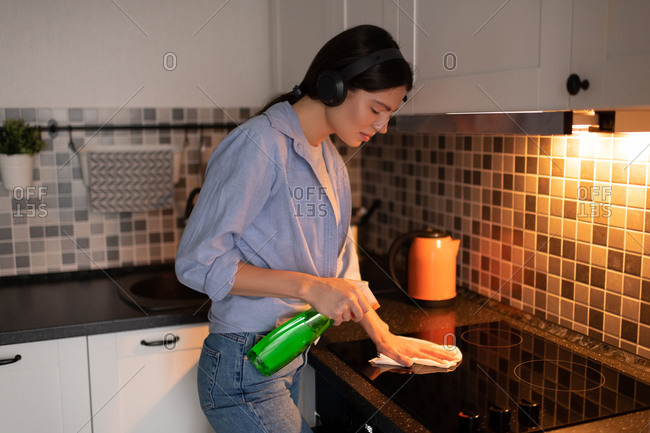 Woman with headphones cleaning stove in kitchen