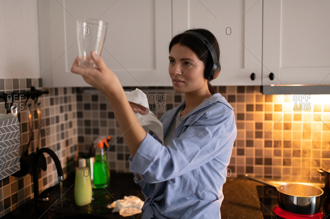 Attentive housewife cleaning and checking glass in kitchen