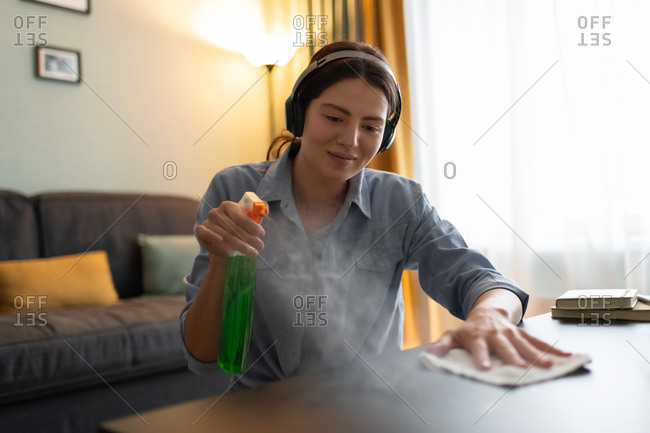 Smiling woman cleaning furniture with spray detergent