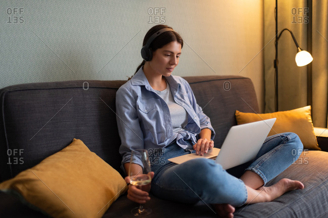 Young woman drinking wine and watching film on laptop at home