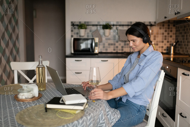 Woman resting in kitchen and browsing internet on laptop