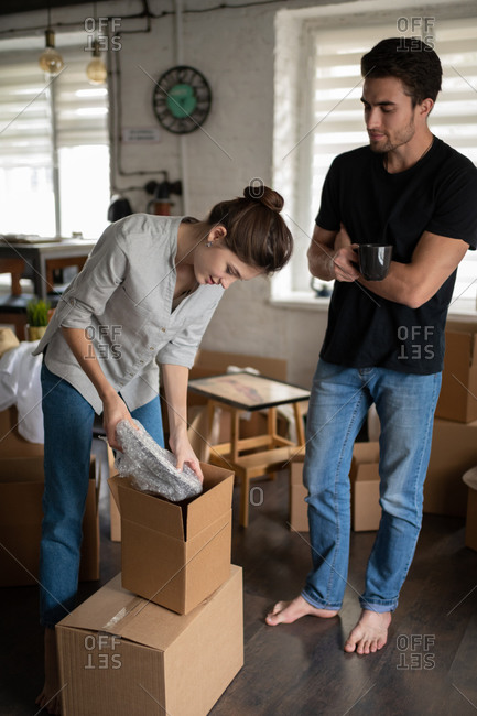 Young couple unpacking dishware in new flat