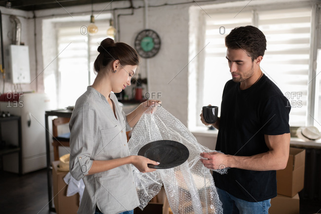 Young couple unwrapping dishware in new apartment