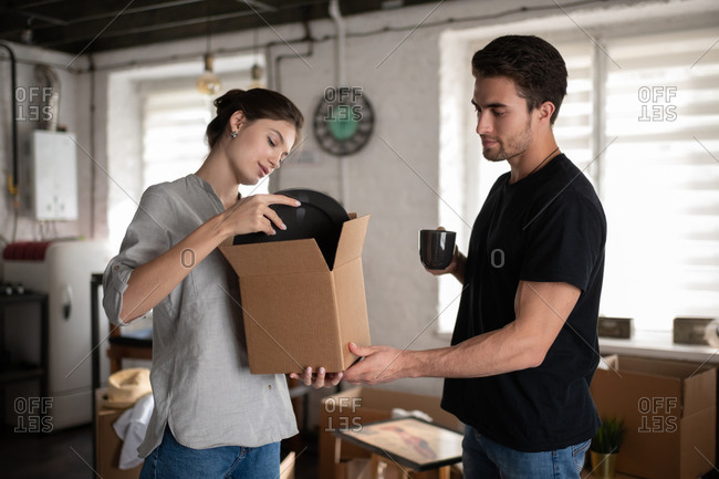 Young couple unpacking plates during relocation
