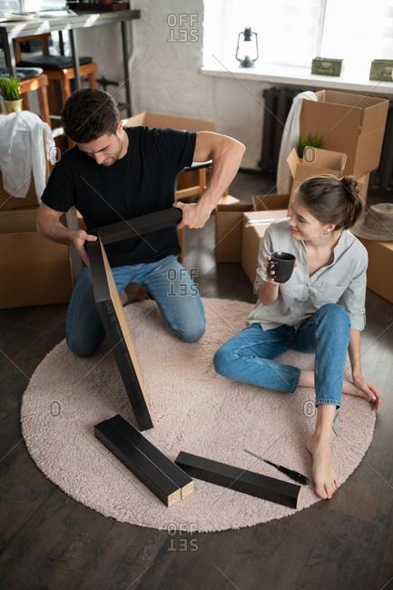 Woman watching man assembling furniture
