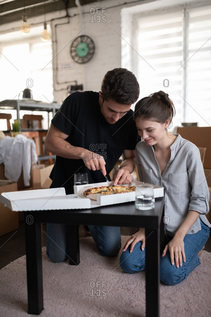 Young couple cutting pizza during relocation