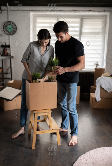 Barefoot couple unpacking plants in new apartment