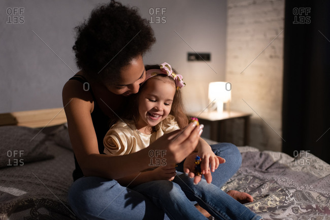 Cheerful ethnic mother and daughter lying in bed before sleep