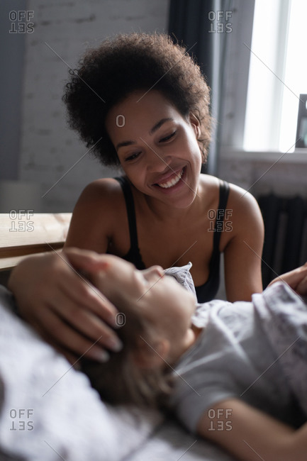 Happy ethnic mother waking up daughter in morning