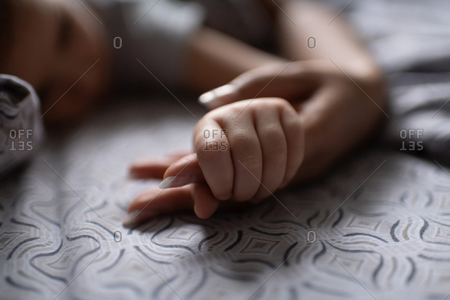 Unrecognizable child grasping finger of mother