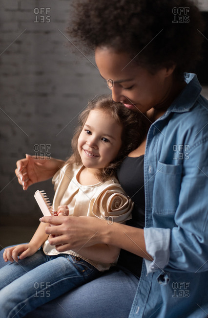 Ethnic mother teaching daughter to comb hair