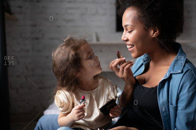 Mother teaching daughter to apply lipstick