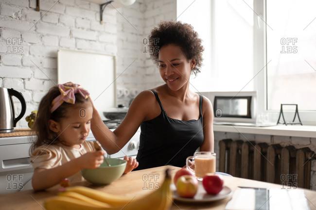Ethnic mother stroking daughter during breakfast
