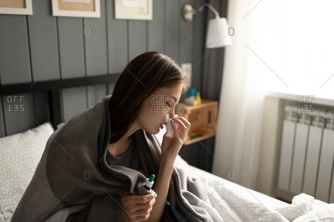 Ill woman blowing nose on bed