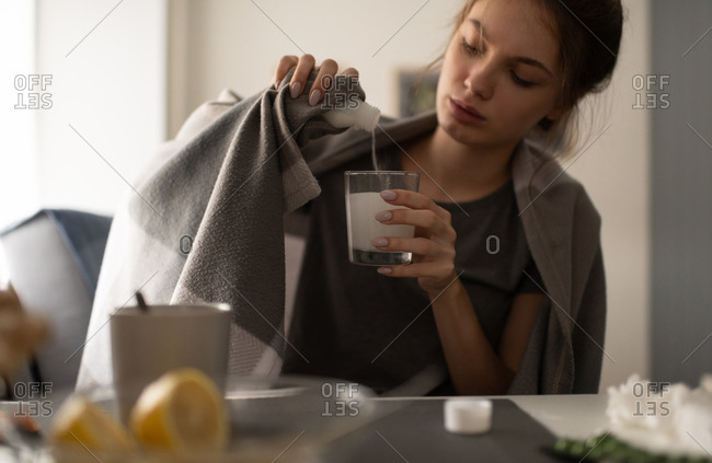 Young woman pouring medicine into glass