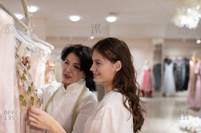 Female customer choosing outfit with help of shop assistant