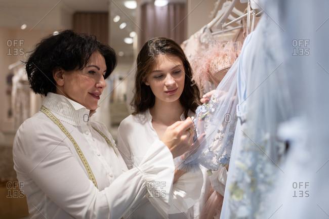 Atelier owner helping client in choosing dress