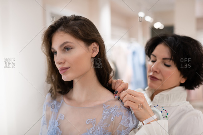 Charming woman trying on tailor made dress with female assistant