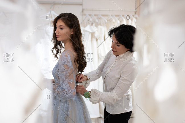 Dress designer with female client trying on dress in atelier