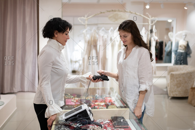 Woman paying with contactless credit card in fashion boutique