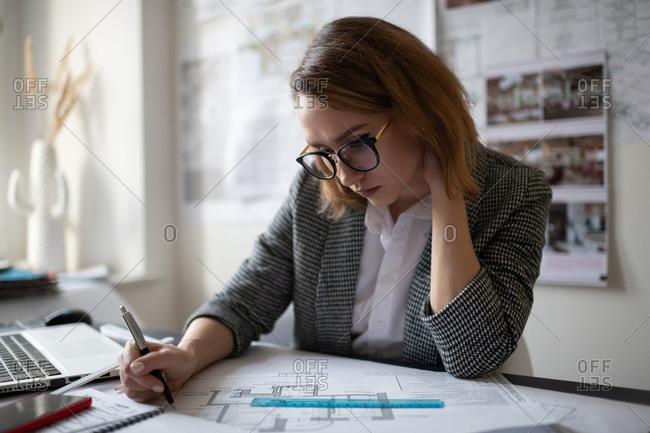 Thoughtful female architect examining draft