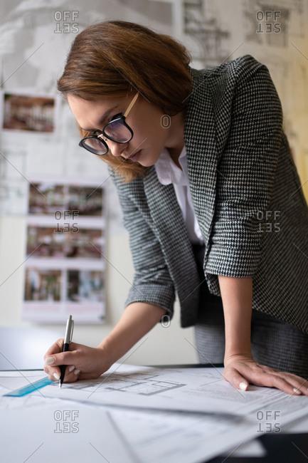 Smart architect making marks on blueprint