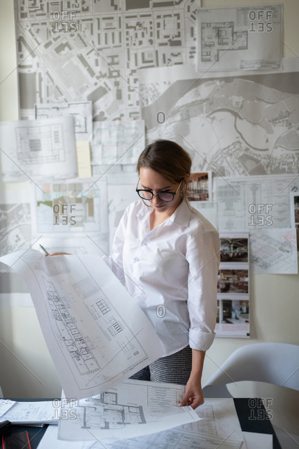 Young female architect working with blueprints