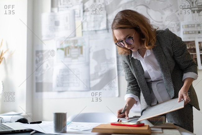 Serious businesswoman with clipboard reading notes on smartphone